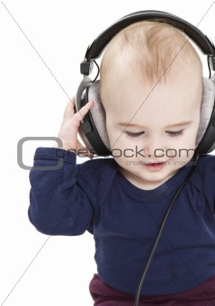 young child with ear-phones listening to music