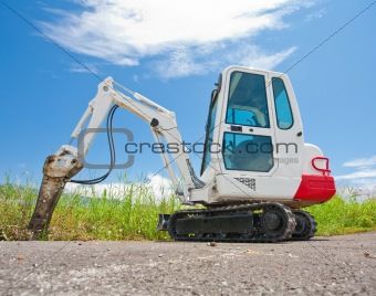 Small caterpillar tractor stands on the asphalt against the blue