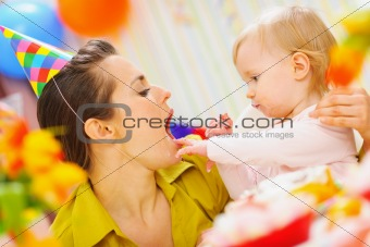 Baby feeding mother with birthday cake