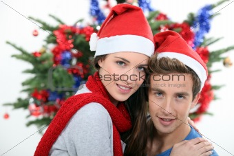 Festive couple in front of Christmas tree