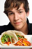 Young man holding up plate of tacos