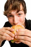 Young man eating his sloppy burger