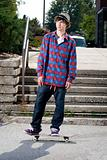 Fashionable skateboarder standing on board