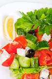 juicy fresh Greek salad in white bowl, on a white background, close-up