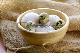chicken and quail eggs in wooden bowl - a rustic style