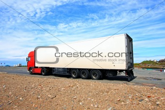 A big red and white lorry against blue sky