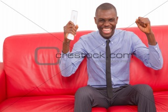 man on the sofa with remote control rejoice