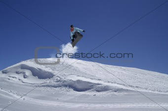 Snowboarder jumping in terrain park