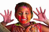 Close up face of young boy playing Holi, smiling with colors on