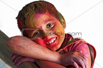 Close up face of young boy playing Holi, smiling colors, white B