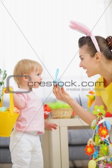 Mother helping baby collecting Easter eggs