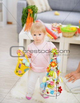 Baby holding basket of Easter eggs and decoration