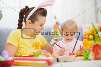 Mother and baby painting on Easter eggs