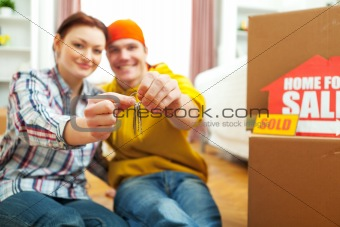 Happy young couple showing home keys