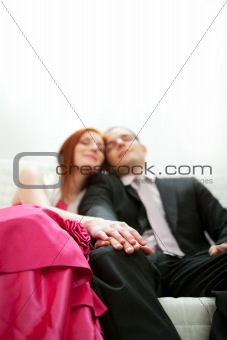 Closeup on hands of formally dressed romantic couple