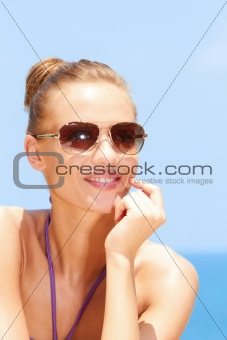 Pretty woman at the beach with sunglasses