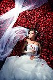 bride is lying in flowerbed