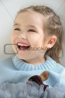  girl child is sitting on the window and laughs