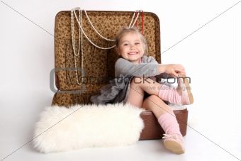 girl sitting in a suitcase on the skin of the bear