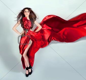 flexible girl moves in a red long dress