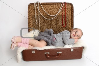 the girl was tired and lay down to rest in a suitcase
