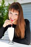 beautiful girl drinking a milkshake with a straw