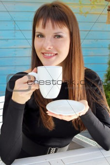 girl holding a cup of drink and smiled pleasantly
