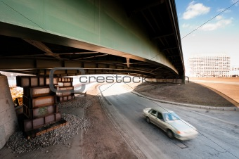 Blurred car moving under an old bridge