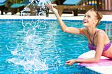 Happy woman splashing water in pool
