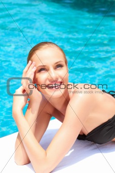Beauty lying next to swimming pool