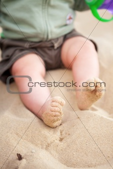 Baby feet covered in beach sand