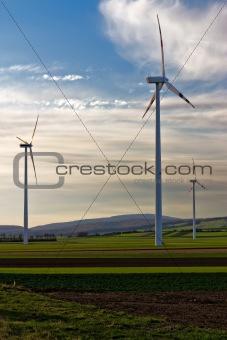 three wind turbines of wind farm in the field