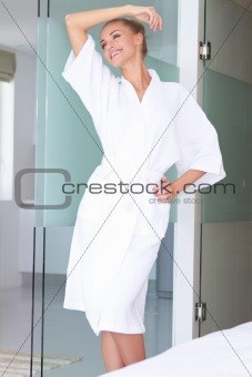 Smiling woman standing in white bathrobe