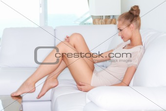 Beautiful introspective woman on white sofa