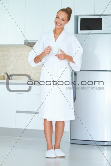 Woman in white robe drinking coffee