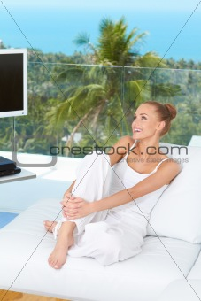 Beautiful happy woman on white sofa
