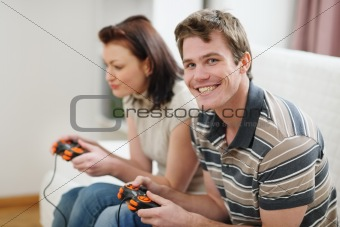 Young man playing on console with girlfriend