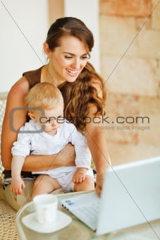 Young mother working with baby on laptop