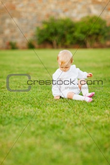 Baby sitting on grass