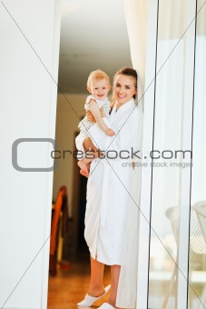 Smiling mother in bathrobe with baby looking out from window