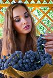 Portrait of a beautiful girl with grapes in vase