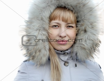 Portrait of young girl in a jacket with a fur hood