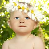 Smiling baby in a flower wreath in green summer background