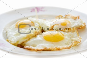 Three eggs on a plate isolated on white