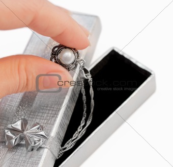 Closeup of hand holding a necklace with one pearl isolated on white