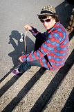Skateboarder sitting on stairs with sunglasses on