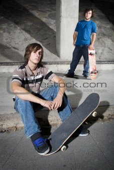 Two skateboarders in underground parking lot