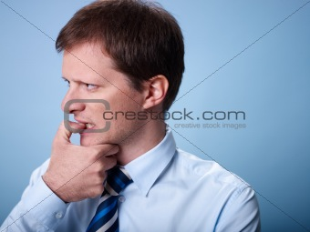 nervous business man biting finger nails