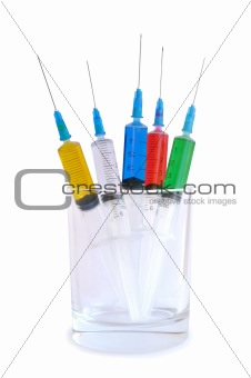 Five disposable syringes in a glass