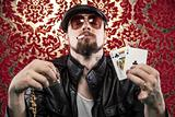 Gangster Looking Man Holding Poker Cards and His winnings